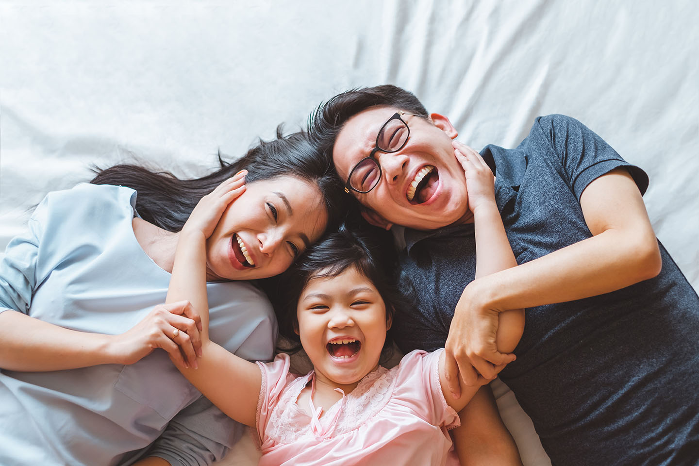 Happy family laying on bed in bedroom with happy and smile